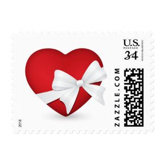 Franqueo rojo del corazón de la tarjeta del día de