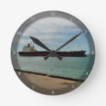 Freighter ship sailing on sea wall clocks