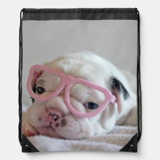 French bulldog white cub Glasses, lying on white Drawstring Bag