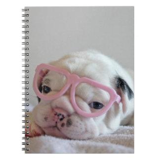 French bulldog white cub Glasses, lying on white Notebook