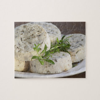 French goat cheese - chevre - with herbs on a jigsaw puzzle