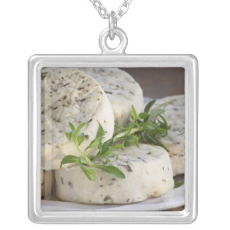 French goat cheese - chevre - with herbs on a square pendant necklace