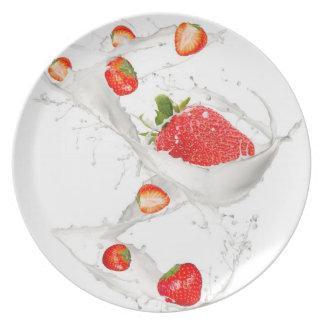 Fresas en chapoteo de la leche platos