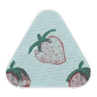 Fresas rosadas tejadas en fondo de los azules altavoz bluetooth