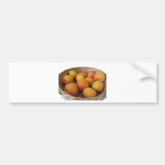 Fresh apricots in a wicker basket on white bumper sticker