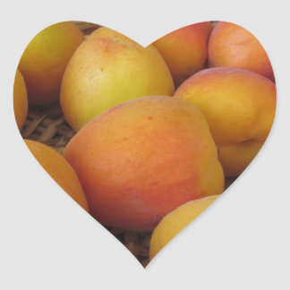 Fresh apricots in a wicker basket on white heart sticker