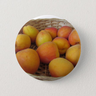 Fresh apricots in a wicker basket on white pinback button