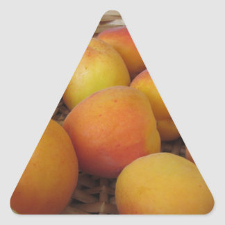 Fresh apricots in a wicker basket on white triangle sticker