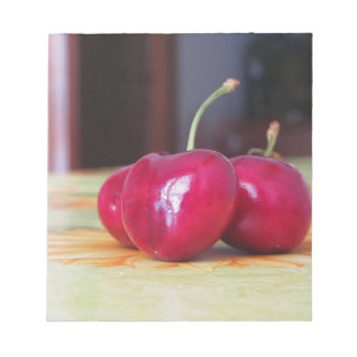 Fresh cherries on the table notepad