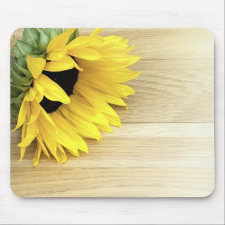 Fresh cut flower laying on a wooden table in sunli mouse pad