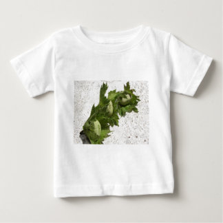 Fresh green hazelnuts on the floor baby T-Shirt