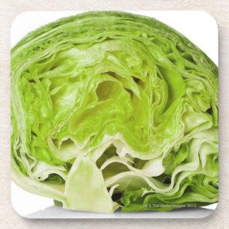 Fresh iceberg lettuce cut in half, on white beverage coaster