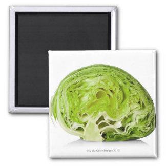 Fresh iceberg lettuce cut in half, on white magnet