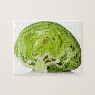 Fresh iceberg lettuce cut in half, on white puzzle