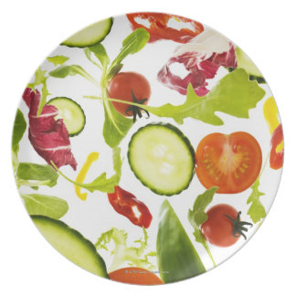 Fresh mixed salad vegetables falling to camera dinner plate