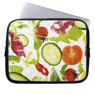 Fresh mixed salad vegetables falling to camera laptop sleeve