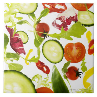Fresh mixed salad vegetables falling to camera large square tile