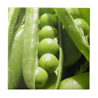 Fresh open green pea pods in sunlight small square tile