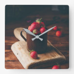 Fresh red strawberries in metal mug on table. square wall clock