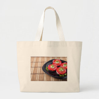 Fresh sliced tomatoes on a black plate close-up large tote bag