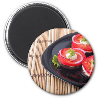 Fresh sliced tomatoes on a black plate close-up magnet