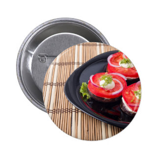 Fresh sliced tomatoes on a black plate close-up pinback button