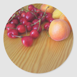 Fresh summer fruits on light wooden table classic round sticker