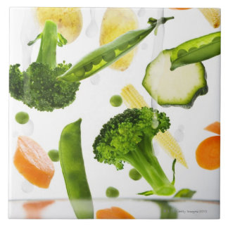 Fresh vegetables with water falling into a bowl tile