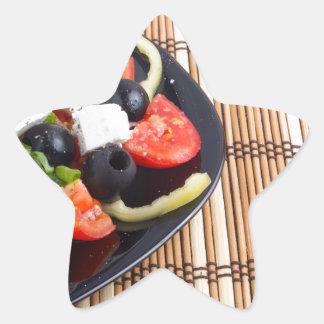 Fresh vegetarian salad in a black plate on a mat star sticker