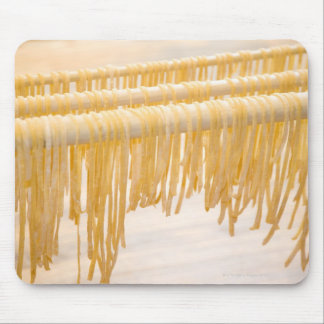Freshly made pasta drying on a wooden rack mouse pad