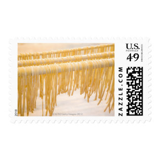 Freshly made pasta drying on a wooden rack postage stamp