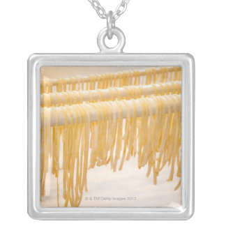 Freshly made pasta drying on a wooden rack square pendant necklace