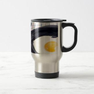 Fried egg with yolk on a black plate travel mug