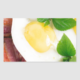 Fried eggs and bacon with herbs and lettuce rectangular sticker