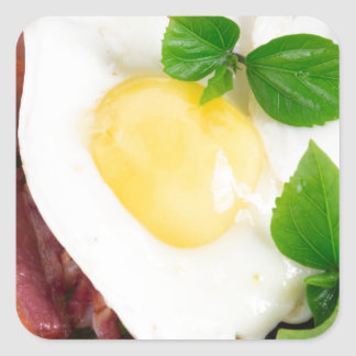 Fried eggs and bacon with herbs and lettuce square sticker