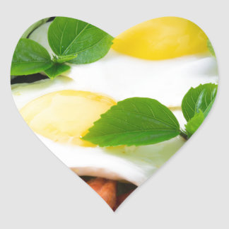 Fried eggs with herbs, lettuce and  bacon heart sticker