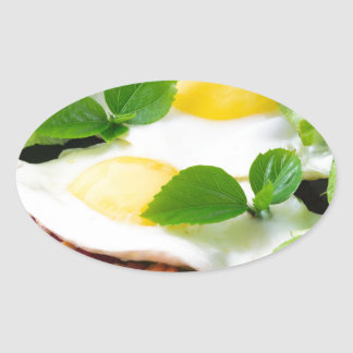 Fried eggs with herbs, lettuce and  bacon oval sticker