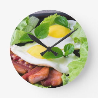 Fried eggs with herbs, lettuce and  bacon round clock