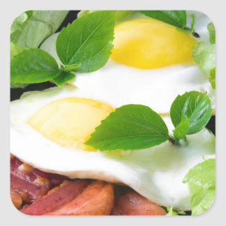 Fried eggs with herbs, lettuce and  bacon square sticker