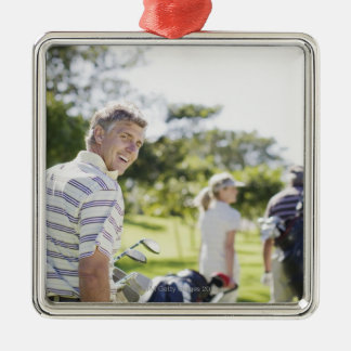 Friends carrying golf bags metal ornament