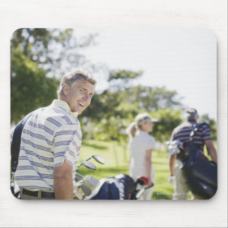 Friends carrying golf bags mouse pad