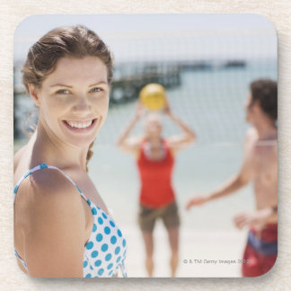 Friends playing volleyball at beach drink coaster
