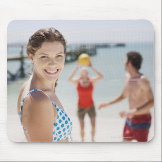 Friends playing volleyball at beach mouse pad