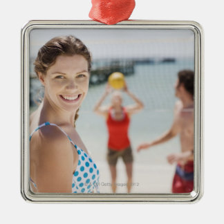 Friends playing volleyball at beach ornament