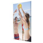 Friends playing volleyball on beach canvas print