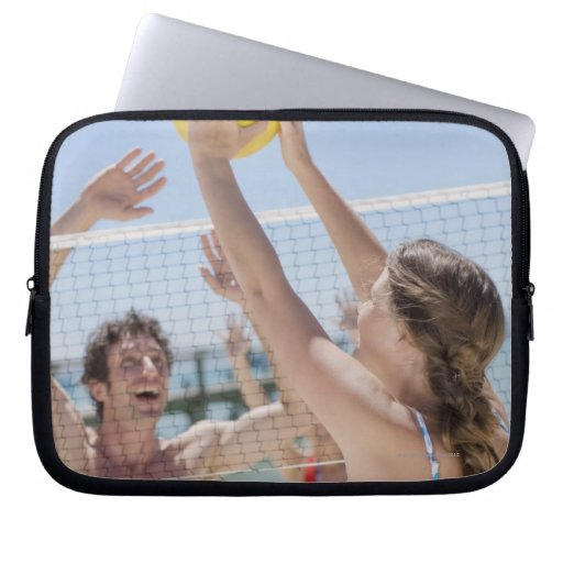 Friends playing volleyball on beach laptop sleeve
