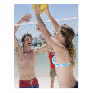 Friends playing volleyball on beach postcard