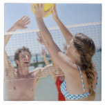 Friends playing volleyball on beach large square tile