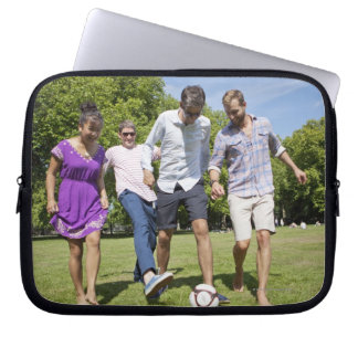 Friends Playing with a Football in a City Park Laptop Sleeves
