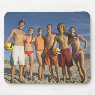 Friends posing on beach with volleyballs mouse pad